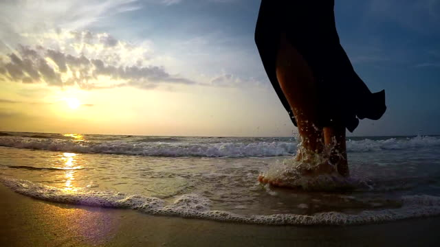 Slow-motion footage of a woman walking through water of the waves on the sandy beach