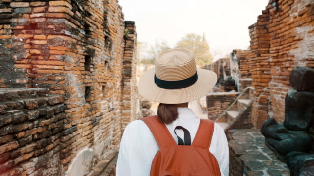 slow-motion footage of traveller with backpack and camera walking in ruins of ayutthaya - пелопоннес стоковые видео и кадры b-roll
