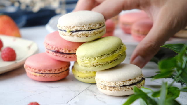 Slow-motion hand pick Colorful French macarons cakes desert set on party table.
