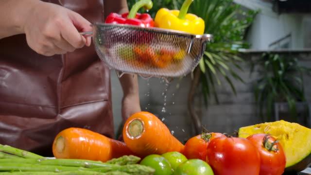 zeitlupe er wäscht obst und gemüse. - vegetarisches gericht stock-videos und b-roll-filmmaterial