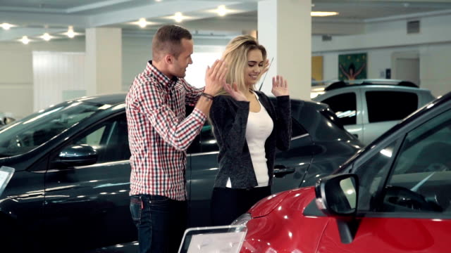 Slowmotion man surprises wife or girlfriend in car dealership, showing new car video