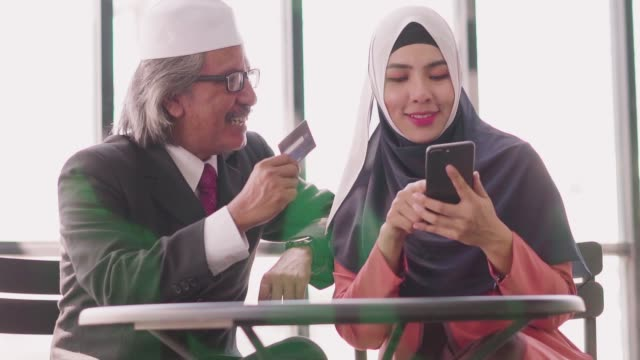 slow-motion: muslim father and daughter shopping online with credit card and smartphone. - holiday and invoice family video stock e b–roll