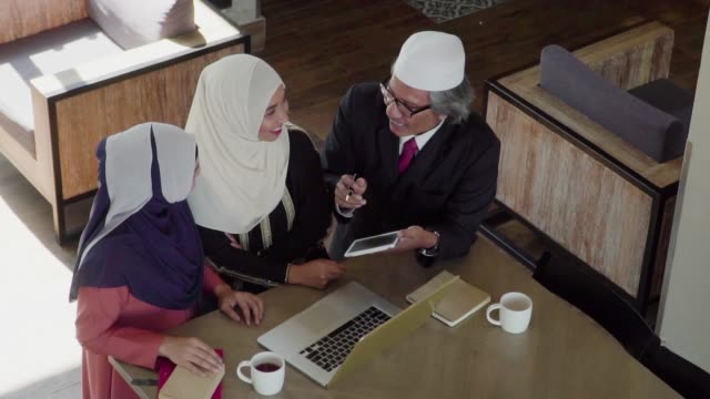 Slow-motion: Muslim people working and discussion with laptop in coffee shop.