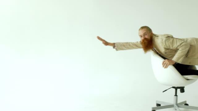 面白い実業家のスローモーションのひげを生やした白い背景の上のオフィスの椅子の上に乗って楽しいを持っています。 ビデオ
