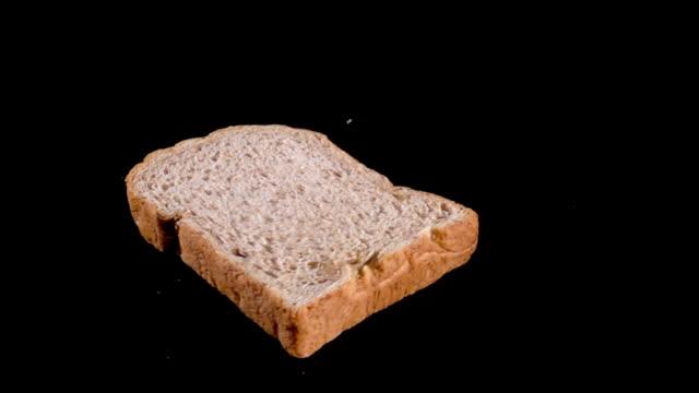 빵의 slowmotion 검은 바닥에 드롭 - 식빵 한 덩어리 스톡 비디오 및 b-롤 화면
