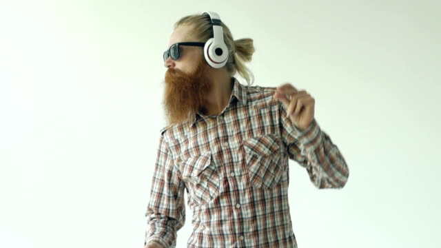 Slowmotion of Happy young bearded man in sunglasses and headphones dancing and listen music on white background video