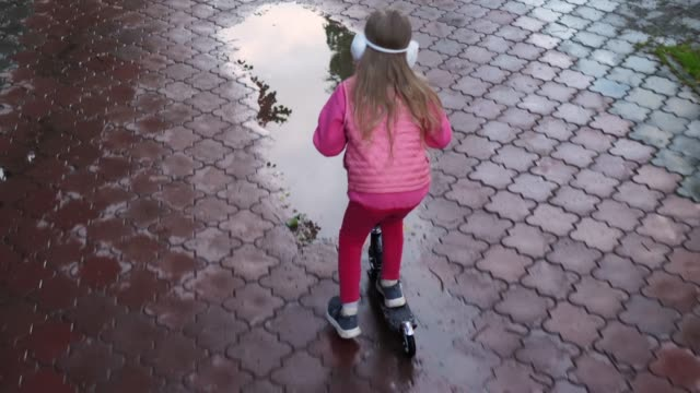 Slow-motion of little girl riding baby scooter in puddles on sidewalk, back view video