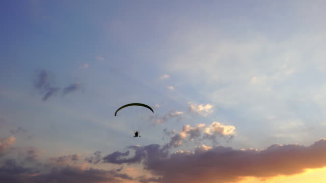 slow-motion of Paraglider flying against a sky at sunset