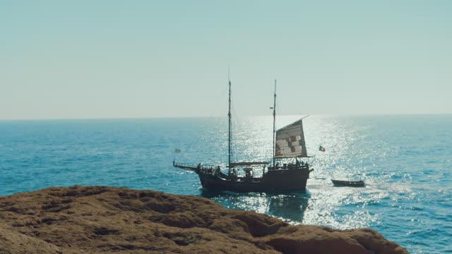 slow-motion av piratbåt som seglar nära stranden en solig dag. stort medeltida fartyg på havet. - segelfartyg bildbanksvideor och videomaterial från bakom kulisserna