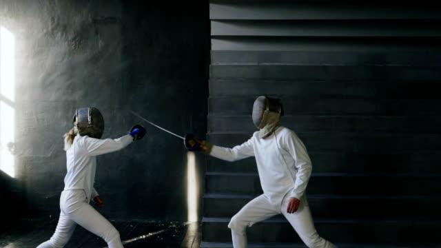 2 スローモーション剣士男と女があるフェンシングの室内トレーニング - デイフェンス点の映像素材/bロール