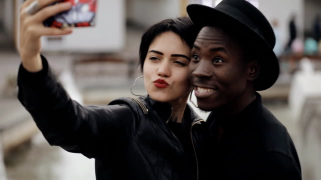 Slowmotion of white woman and black man couple makes selfie video on smartphone. She kiss his cheek. They smiling, laughing together. Slowmotion of white woman and black man couple makes selfie video on smartphone. She kiss his cheek. They smiling, laughing together. young couple stock videos & royalty-free footage
