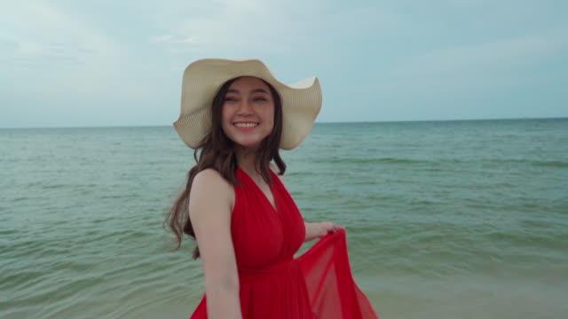 vidéos et rushes de ralenti de la femme avec des bras écartés dans une robe rouge sur la plage de mer avec le coup de vent - bras humain