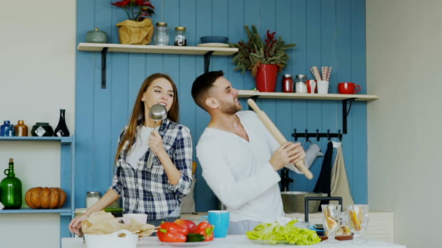 Slowmotion of Young joyful couple have fun dancing and singing while cooking in the kitchen at home video