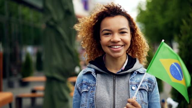 slowmotion porträtt av afroamerikanska kvinna glad turist tittar kameran, leende och hålla brasilianska flaggan stod utanför. turism och människor koncept. - brasilien flagga bildbanksvideor och videomaterial från bakom kulisserna