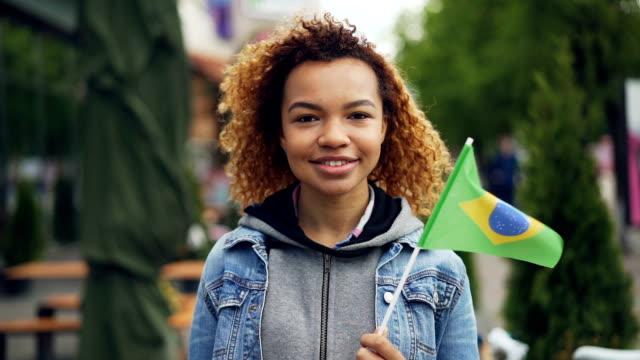 slowmotion porträtt av glada african american tjej tittar på kameran och hålla brasilianska flaggan står i fin park i modern stad. turism och människor koncept. - brasilien flagga bildbanksvideor och videomaterial från bakom kulisserna