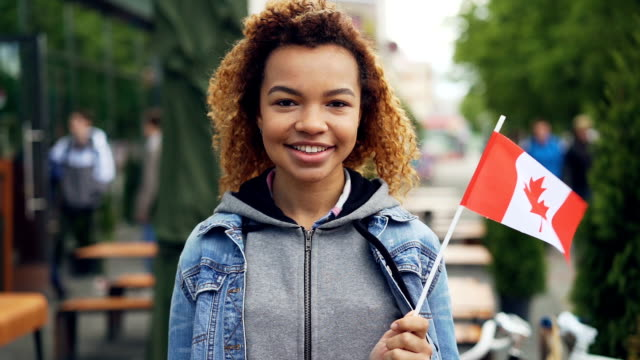 slowmotion portrait of smiling african american girl traveller holding canadian flag and looking at camera outdoors. happy tourist and visiting foreign coutries concept. - canada flag stock videos & royalty-free footage