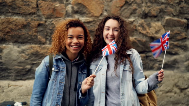 Slowmotion-Porträt der beiden Freundinnen ausländischen Studierenden im Vereinigten Königreich britische Flaggen winken und lachen, Blick in die Kamera. Freundschaft, Tourismus und glückliche Menschen Konzept. – Video
