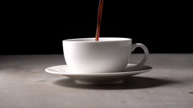 Slowmotion pouring coffee into a glass of coffee.
