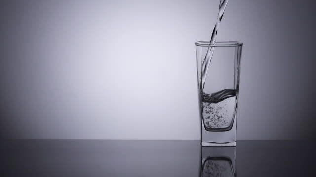 slow-motion, pouring water into a drinking glass. - bicchiere vuoto video stock e b–roll