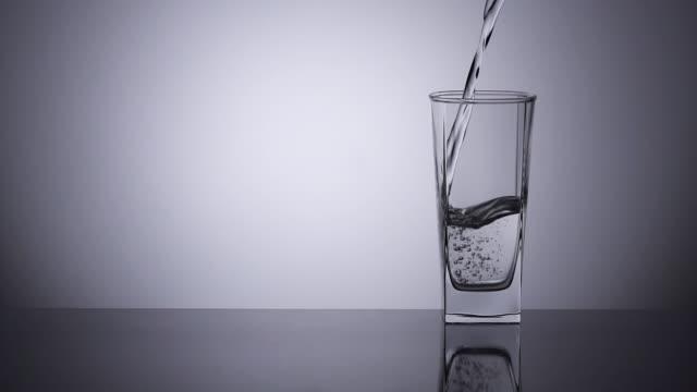 al rallentatore, versando acqua in un bicchiere da bere. - vetro video stock e b–roll