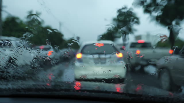 slow-motion, rain drop on windshield with traffic jam
