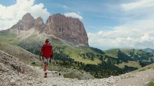 Slow-motion senior man trail hiking on mountain video