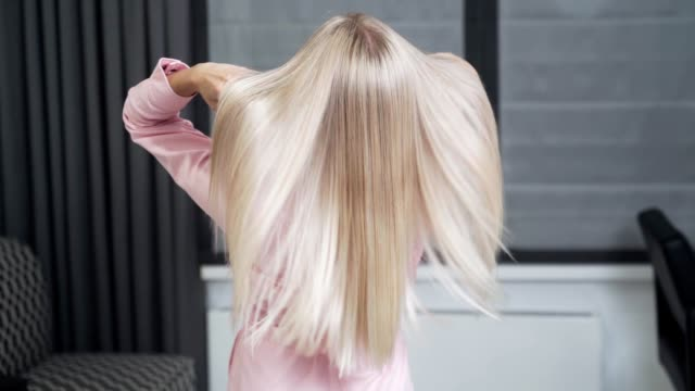 Slow-motion shooting of a long blond hair of a young girl, backside view