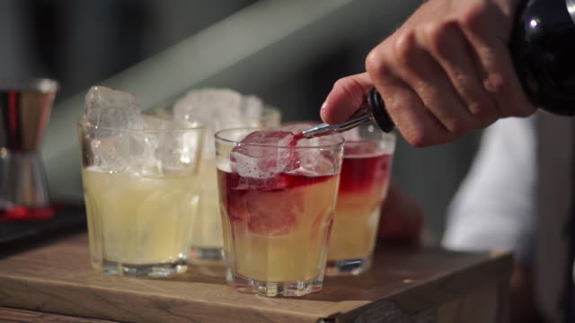 slowmotion shot of a bartender in an outdoor bar pours a cocktail into a glasses video