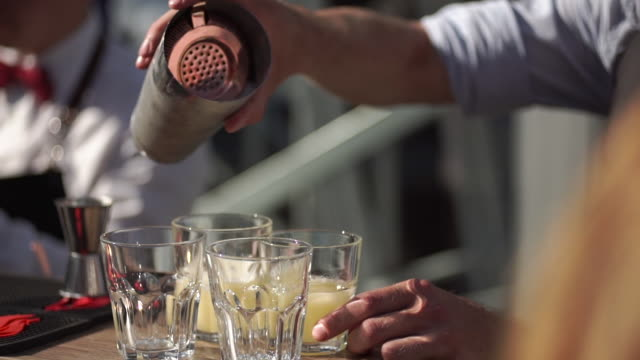 slowmotion shot of a bartender in an outdoor bar pours a cocktail into a glasses - alchol video stock e b–roll