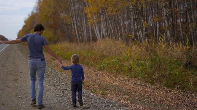Slowmotion shot of a father and his son walking by the road with an autumn forest nearby and lots of yellow leaves falling down on the ground. Autumn travel concept