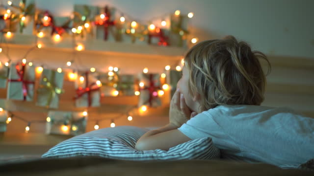 vidéos et rushes de slowmotion a tiré d'un petit garçon regardant un calendrier d'avent accrochant sur un lit alléger avec des lumières de noel. se préparer pour le concept de noel et du nouvel an. concept de calendrier de l'avent - calendrier de l'avent