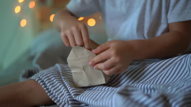slowmotion-aufnahme eines kleinen jungen, der ein geschenk aus einem adventskalender öffnet, der an einem bett hängt, das mit weihnachtsbeleuchtung aufgehellt ist. vorbereitung auf weihnachten und neujahr konzept. adventskalenderkonzept - advent stock-videos und b-roll-filmmaterial