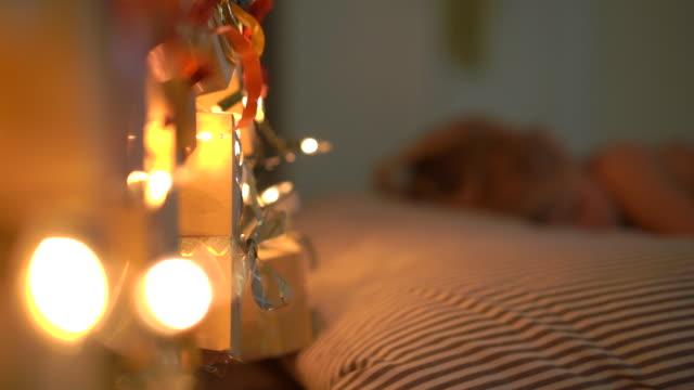 vidéos et rushes de slowmotion shot d'un petit garçon dormant dans son lit avec un calendrier de l'avent éclaircir avec des lumières de noel brille sur un dos de son lit. se préparer pour le concept de noel et du nouvel an. concept de calendrier de l'avent - calendrier de l'avent