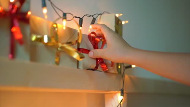 vidéos et rushes de slowmotion photo d'un petit garçon prend un cadeau d'un calendrier de l'avent suspendu sur un lit qui est allégé avec des lumières de noel. se préparer pour le concept de noel et du nouvel an. concept de calendrier de l'avent - calendrier de l'avent