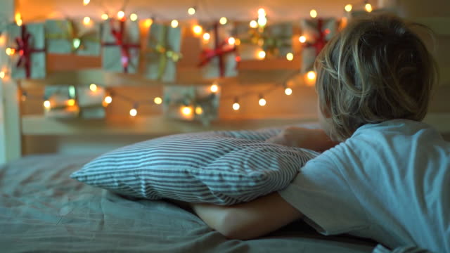 Slowmotion shot of a little boy wakes up and sees an advent calendar hanging on a bed lighten with Christmas lights. Getting ready for Christmas and New Year concept. Advent calendar concept