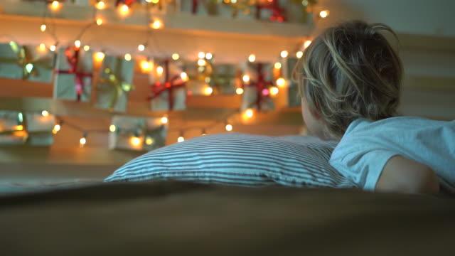 vidéos et rushes de slowmotion photo d'un petit garçon se réveille et voit un calendrier de l'avent suspendu sur un lit éclaircir avec des lumières de noel. se préparer pour le concept de noel et du nouvel an. concept de calendrier de l'avent - calendrier de l'avent