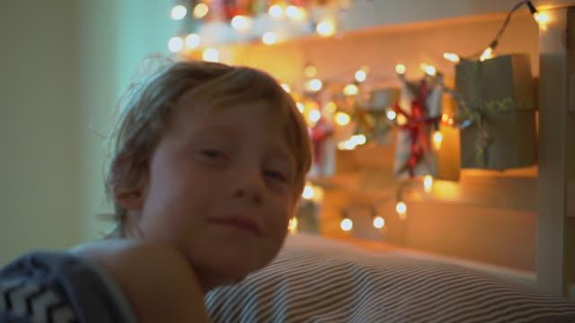 vidéos et rushes de slowmotion shot d'un petit garçon se réveillant dans son lit avec un calendrier de l'avent éclaircir avec des lumières de noel brille sur un dos de son lit. se préparer pour le concept de noel et du nouvel an. concept de calendrier de l'avent - calendrier de l'avent