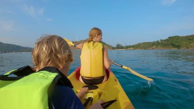 vidéos et rushes de slowmotion photo d'une jeune famille kayak dans une mer tropicale et avoir du plaisir à regarder les récifs coralliens et les poissons tropicaux sous l'eau. plage de ya nui sur l'île de phuket - mer d'andaman