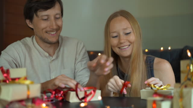 Slowmotion shot of a young woman and man father and mother wrap presents. Presents wrapped in craft paper with a red and gold ribbon for Christmas or new year. Parents make an advent calendar for their children. Advent calendar concept