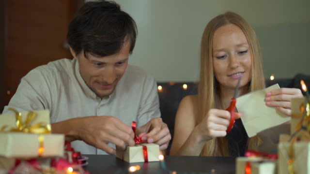 slowmotion schuss einer jungen frau und mann vater und mutter wickeln geschenke. geschenke in handwerkspapier mit einem rot-goldenen band für weihnachten oder neujahr verpackt. eltern erstellen einen adventskalender für ihre kinder. adventskalenderkonzep - adventskalender stock-videos und b-roll-filmmaterial