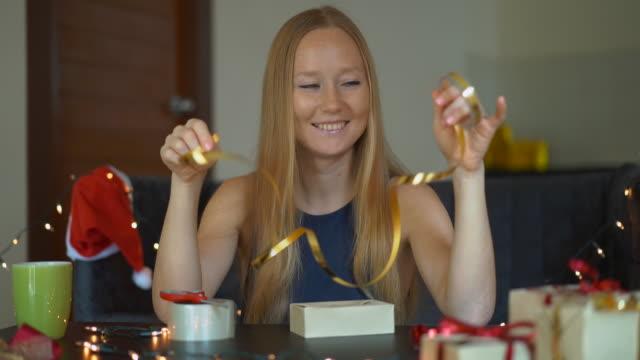 slowmotion-aufnahme einer jungen frau packt geschenke. geschenk verpackt in handwerkspapier mit einem roten und goldenen band für weihnachten oder neujahr. frau macht einen adventskalender für ihre kinder - adventskalender stock-videos und b-roll-filmmaterial