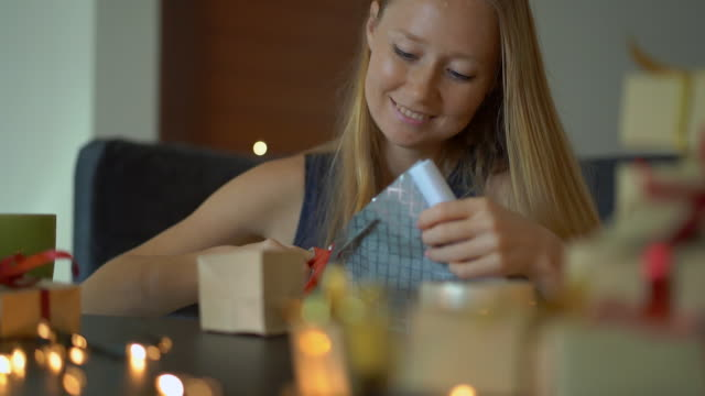 Slowmotion shot of a young woman is packing presents. Present wrapped in craft paper with a red and gold ribbon for christmas or new year. Woman makes an advent calendar for her children