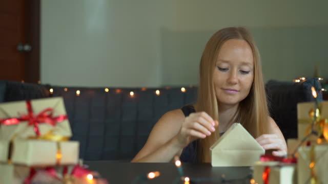 vidéos et rushes de slowmotion photo d'une jeune femme est l'emballage des cadeaux. présent enveloppé dans du papier d'artisanat avec un ruban rouge et or pour noel ou nouvel an. la femme fait un calendrier d'avent pour ses enfants - calendrier de l'avent