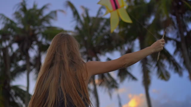 Slowmotion shot of a young woman on a tropical beach with a kite during a sunset time