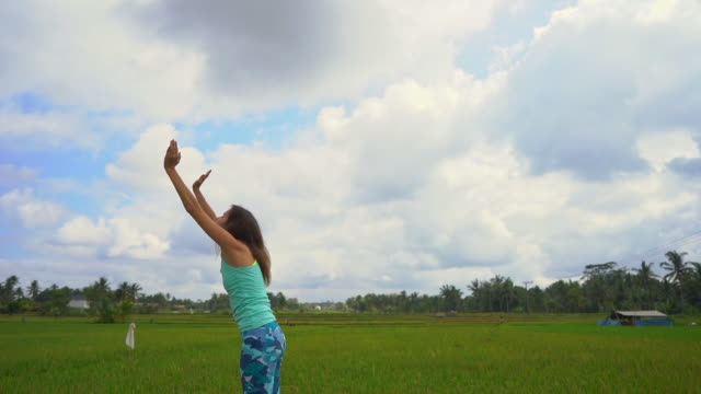 slowmotion shot of a young woman practicing yoga on a beautiful rice field - mudra video stock e b–roll