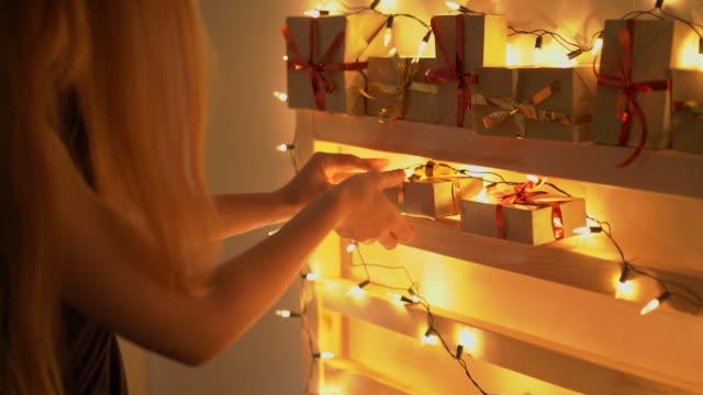 slowmotion-aufnahme einer jungen frau, die einen adventskalender für ihre kinder macht. vorbereitung auf weihnachten und neujahr konzept. adventskalenderkonzept - adventskalender stock-videos und b-roll-filmmaterial