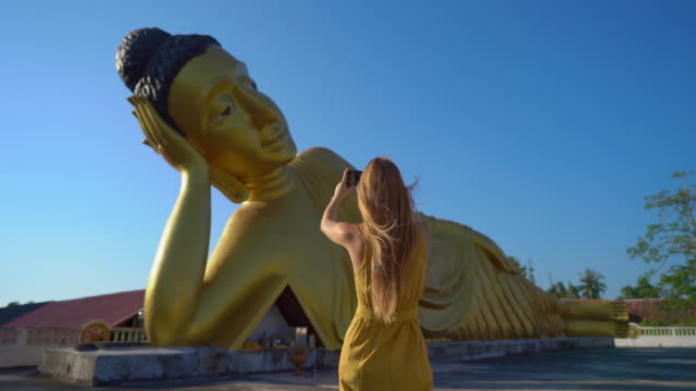 vídeos de stock e filmes b-roll de slowmotion shot of a young woman traveler visiting the the wat srisoonthorn temple with a statue of the lying buddha on phuket island. travell to thailand concept - buda