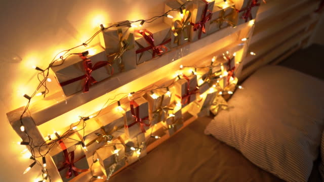 vidéos et rushes de slowmotion photo d'un calendrier de l'avent accroché à un lit qui est allégé avec des lumières de noel. se préparer pour le concept de noel et du nouvel an. concept de calendrier de l'avent - calendrier de l'avent