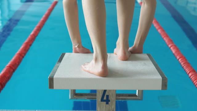 vidéos et rushes de slow-motion capture de professionnel concentré nageuse sur le bloc de départ. - starting block