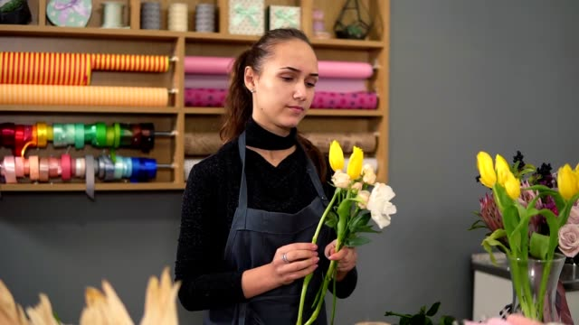 Slowmotion shot of young female florist arranging modern bouquet at flowers shop. She combines creamy roses and yellow tulips video